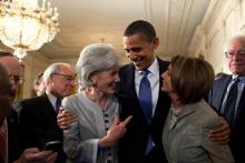 President Barack Obama embraces Secretary of Health and Human Services Kathleen Sebelius, left, and House Speaker Nancy Pelosi after signing the health insurance reform bill.Official White House Photo by Pete Souza